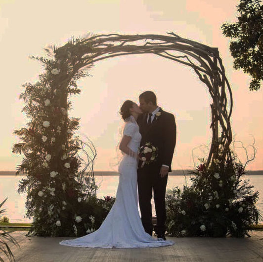 Bride and groom under circle driftwood wedding arch